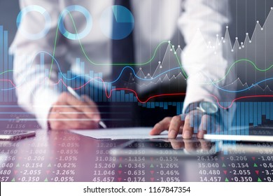 Graphs and businessman signing document at table on background. Financial trading concept