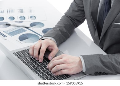 Graphs and charts analyzed by businessman on table