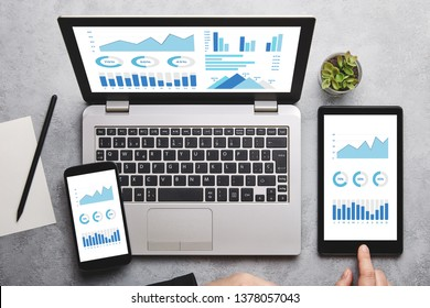 Graphs and charts elements on laptop, tablet and smartphone screen over gray table. Flat lay