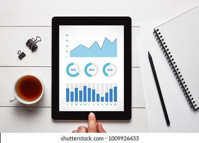 Graphs and charts elements on tablet screen with office objects on white wooden table. All screen content is designed by me. Flat lay