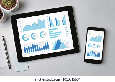 Graphs and charts elements on tablet and smartphone screen over gray table. All screen content is designed by me. Flat lay