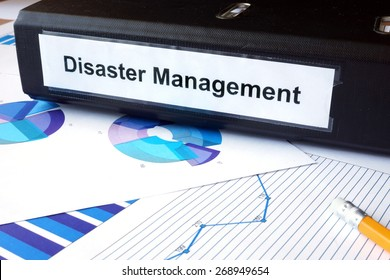 Graphs and file folder with label  Disaster Management. Business concept.