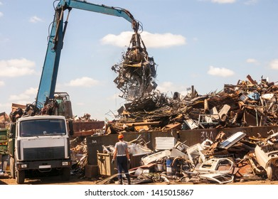 A grapple truck and a man in an orange helmet work on a hot sunny day at a large scrap yard.