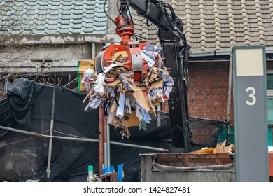Grappling claw-machine collecting trash for recycling in front of an old, abandoned house in South Korea