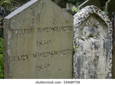 Grasmere, England - May 30, 2012: In the cemetery of the Saint Oswald Church stands the gray old tombstone of the poet William Wordsworth and his wife Mary Hutchinson. Other tombstone with Agnus Dei.