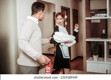 Grasping arm. Man grasping arm of young housekeeper feeling scared while planning harassing her