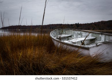 Grass and a abandoned boat looking towards a body of water (lake)