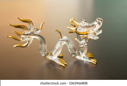 A grass Chinese dragon mad by glassblowing put on oak color table.