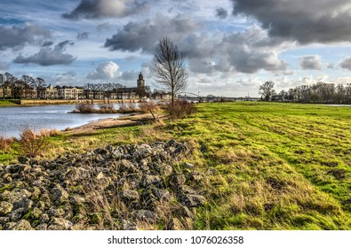 Grass covered floodplains of the IJssel river at low tide with the city of Deventer, The Netherlands in the background
