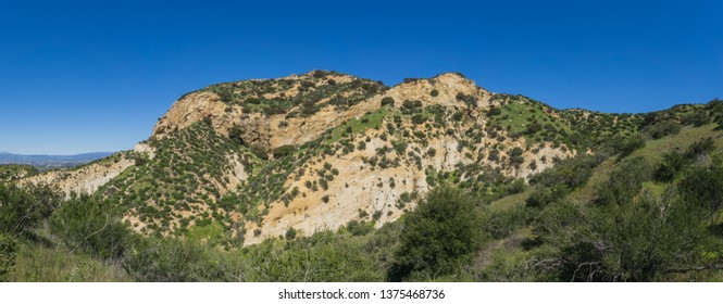 Grass covered hills lead up to the slopes of a rock canyon in California near Santa Clarita.