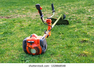 Grass cutter / brush cutter for trimming overgrown grass lay on the lawn