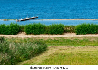 Grass field and jetty in lake called Veerse Meer. Veere, The Netherlands