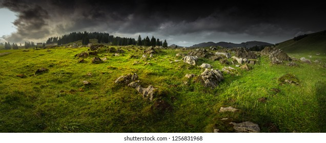 Grass field and mountain with storm