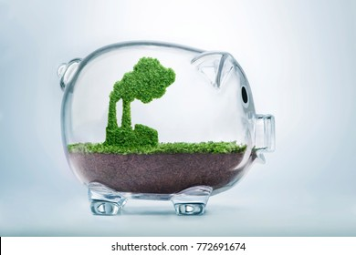Grass growing in the shape of a factory, inside a transparent piggy bank, symbolising the need to invest in the protection of the environment and to reconnect with nature.