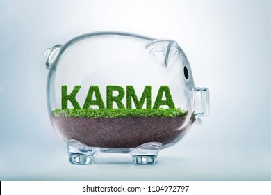 Grass growing in the shape of the word karma, inside a transparent piggy bank.