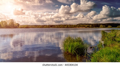 Grass and lake during sunset. Beautiful natural landscape. dramatic sky. Fantastic views of the Lake in the forest. under sunlight. Dramatic and picturesque scene. artistic images. beauty of the world