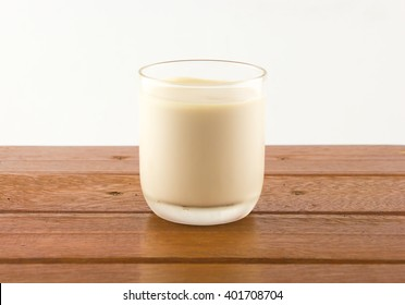 A grass of milk on wooden table
