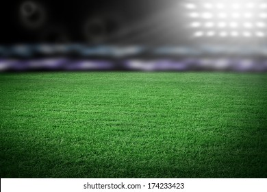 Grass on stadium in spotlight with spectators