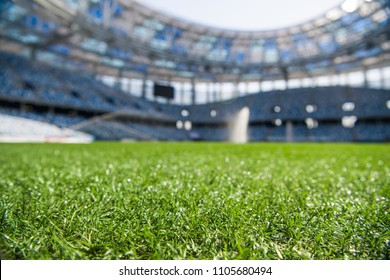 Grass on stadium in sunlight. Closeup of a green football field. Wet stadium grass in the morning light during watering irrigation. Close up macro of soccer or football field. green grass field
