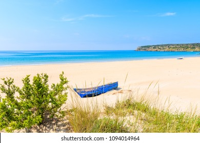 Grass sand dune and fishing boat on white sand Bolonia beach, Andalusia, Spain