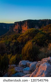 Grass and shrubbery growing on craggy cliffs at sunset in the Blue Mountains National Park in Katoomba, Australia. Stone boulders colored by red evening sun