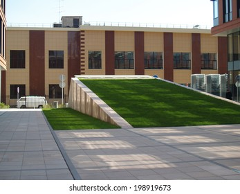 Grass slide in  inner yard of a city building with square spots of lights and shades