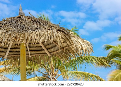 Grass Thatch Roof Hut with Beautiful Tropical Blue Sky in background