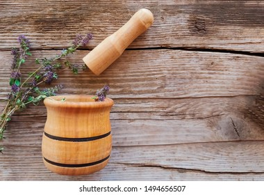 grass thyme with mortar and pestle on wooden background with copy space