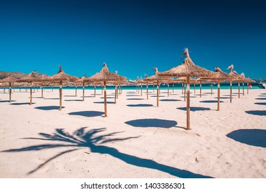 Grass umbrellas at the summer beach on Playa de Muro. Mallorca, Spain