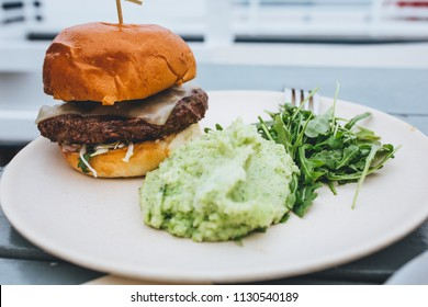 grass-fed beef burger with brioche bun, havarti cheese, pepperoncini aioli, tomato, arugula, red onion, and cabbage slaw. side of broccoli mashed potatoes and arugula salad. organic meal