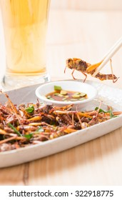Grasshopper fried in chopstick on wood background
