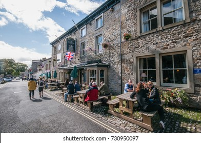 GRASSINGTON, UNITED KINGDOM - 11 SEPTEMBER 2017: People socializing on a sunny day outside a traditional English pub in a rural town Grassington, located in Yorkshire Dales National Park