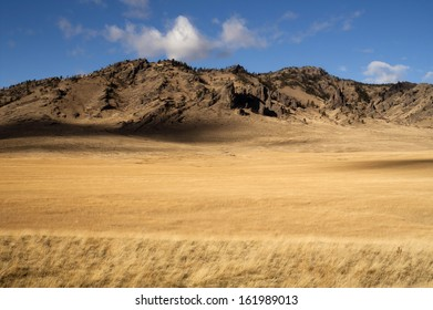 Grassland leads up to rocky mountain hillside in this northern rural landscape