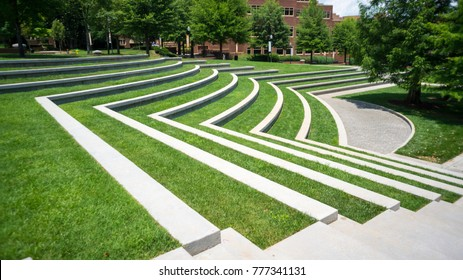 a grassy Amphitheatre with trees on the side
