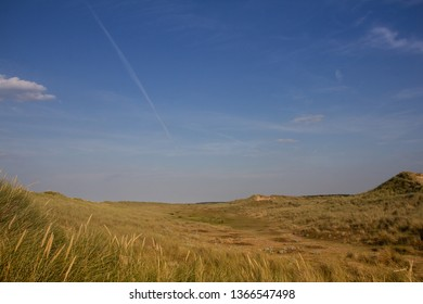 Grassy dunes at Burnham Overy Staithe with plane trail like meteorite.