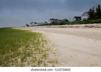 A grassy growth rises out of the sand as an overcast sky hints at the potential danger to homes along the Atlantic shoreline which stand above the reach of high tide, protected by large boulders