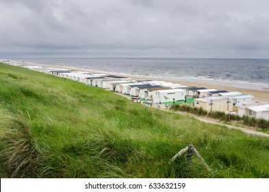 Grassy Hill Overlooking a Sandy Beach full of Trailers in The Netherlands.