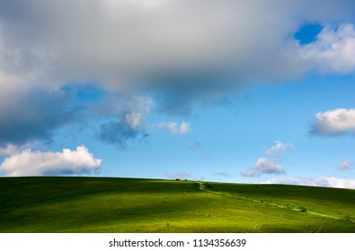 grassy hillside and gorgeous afternoon cloudscape. countryside road winds uphill in to the distance. wonderful nature background.