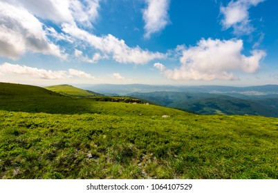 grassy hillside meadow in the morning. mountain peak in the distance under the blue sky with fast moving clouds