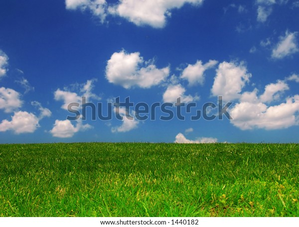 Grassy knoll with clouds in blue sky