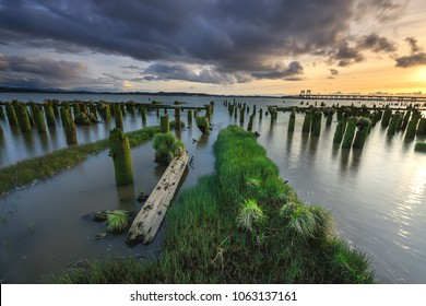 Grassy path leads the eye to the water at sunset in Astoria, Oregon.