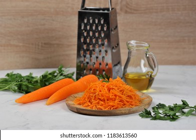 Grate the carrots on a wooden tray. In the background a grater, a few carrots, a bunch of parsley, a jug with olive oil. Light background. Close-up.