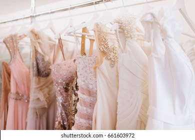 Grate choice of gorgeous fashion dresses hanging on racks in woman's wardrobe. A big variety of sparkling clothes. Difficult choice, women's dream