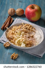 Grated apple with walnut and yogurt on blue table