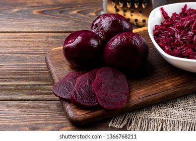 Grated boiled beet on dark wooden background.