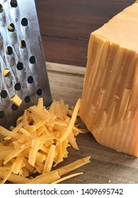 grated cheddar cheese, close up with the grater and the block of cheese