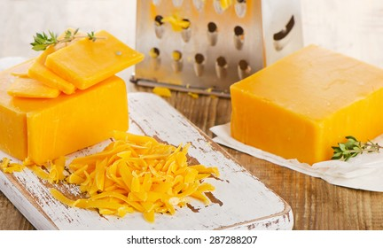 Grated Cheddar Cheese on  a wooden Cutting Board. Selective focus