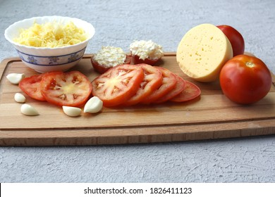 Grated cheese, pressed garlic and chopped tomatoes. Concept - preparing a snack.