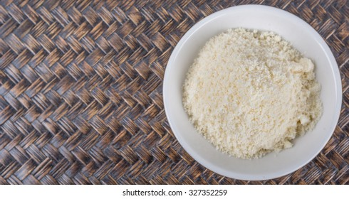 Grated cheese in white bowl over wicker background