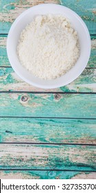 Grated cheese in white bowl over wooden background